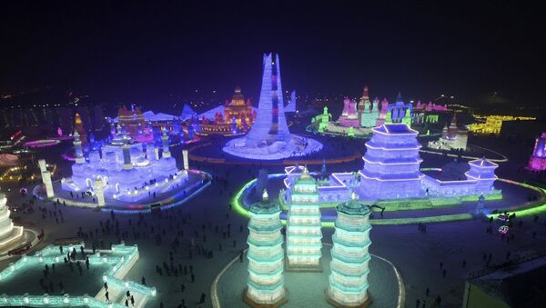 People visit ice sculptures illuminated by coloured lights during a trial operation of the upcoming Harbin International Ice and Snow Festival, in Harbin, Heilongjiang province, China - Sputnik Italia