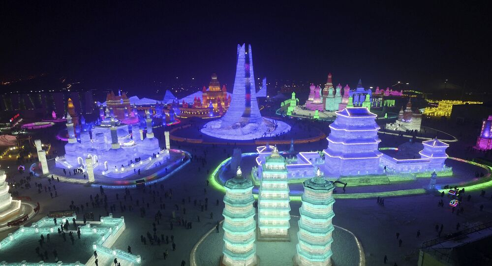 People visit ice sculptures illuminated by coloured lights during a trial operation of the upcoming Harbin International Ice and Snow Festival, in Harbin, Heilongjiang province, China