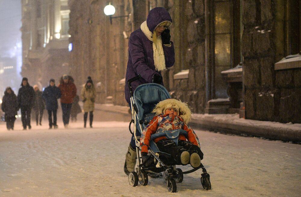 Una donna passeggia con suo figlio sotto la neve a Mosca.