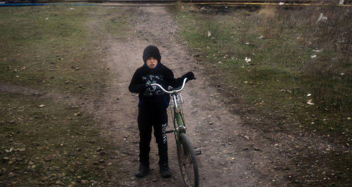 Un bambino in bicicletta nella campagna fuori da Lugansk