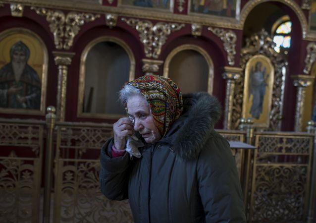 La donna nella chiesa distrutta a Donbass