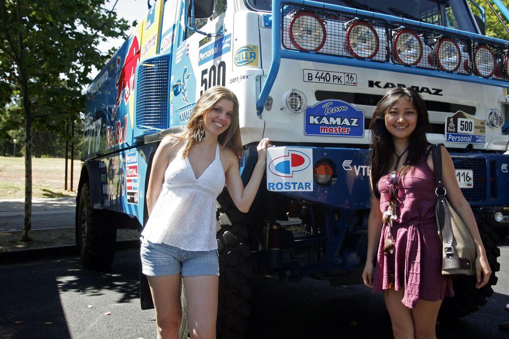Due ragazze brasiliane posano vicino a un camion della squadra KAMAZ-Master.