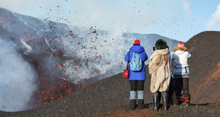 Un gruppo di donne fotografa da vicino l'eruzione del vulcano Plosky Tobalchik volcano in Kamchatka