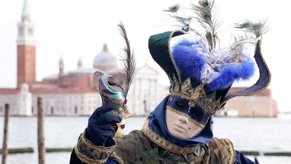 A masked reveller poses in front of St. Mark's square during the first day of carnival - Sputnik Italia