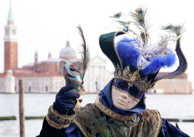 A masked reveller poses in front of St. Mark's square during the first day of carnival