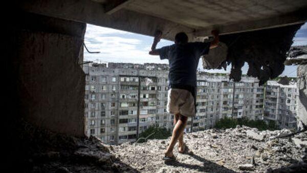 Мужчина осматривает повреждения в жилом доме, после артиллерийского обстрела квартала Мирный в Луганске - Sputnik Italia