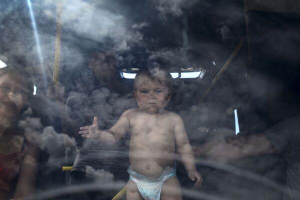 Un bambino su un autobus destinato al trasporto dei profughi a Lugansk. - Sputnik Italia