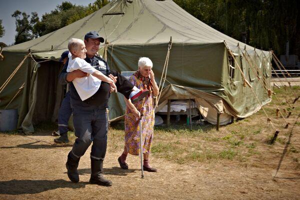 Un operatore della protezione civile ucraina trasporta in braccio una signora anziana in un campo profughi vicino a Lugansk. - Sputnik Italia