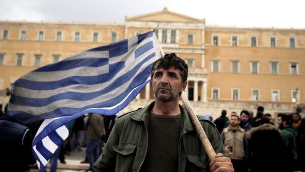 Un agricoltore greco tiene la bandiera greca di fronte al parlamento durante le proteste contro le riforme delle pensioni, il 12 febbraio, 2016 - Sputnik Italia