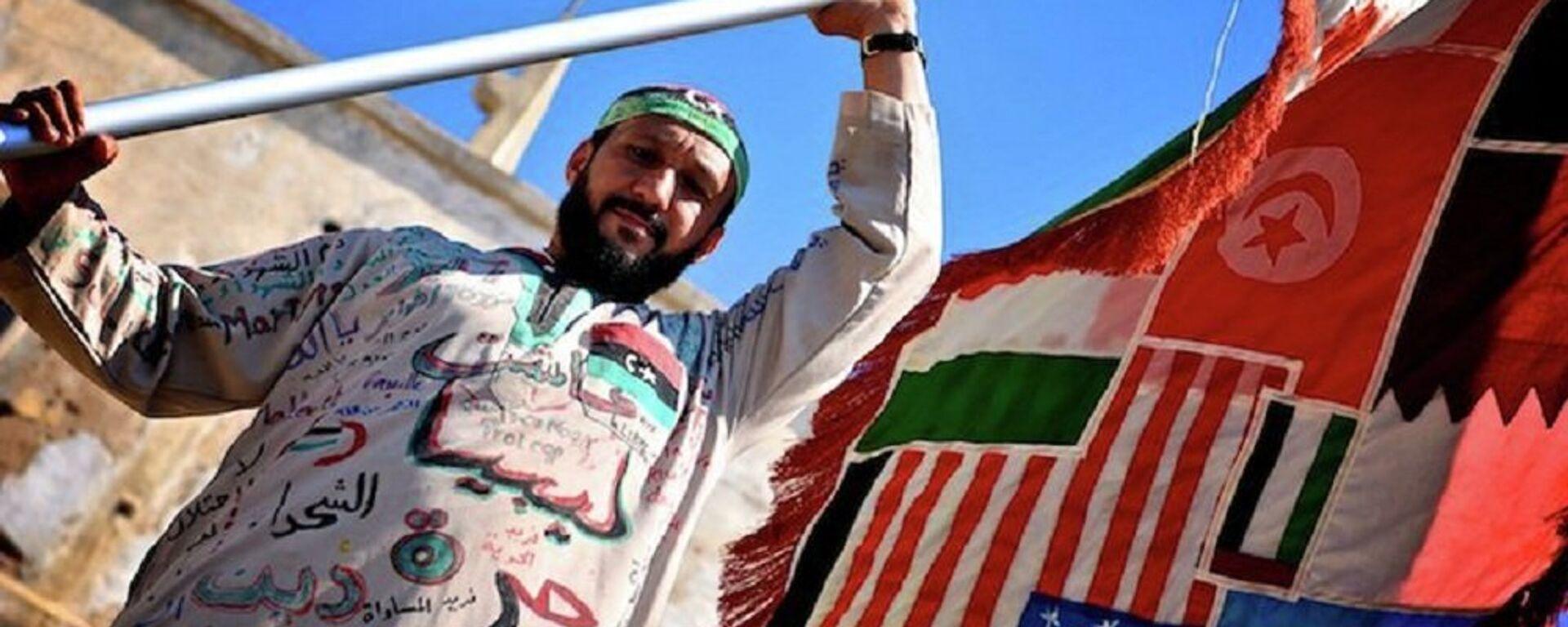 Un uomo tiene la bandiera di tutti i paesi coinvolti nella guerra civile in Libia - Sputnik Italia, 1920, 10.06.2021