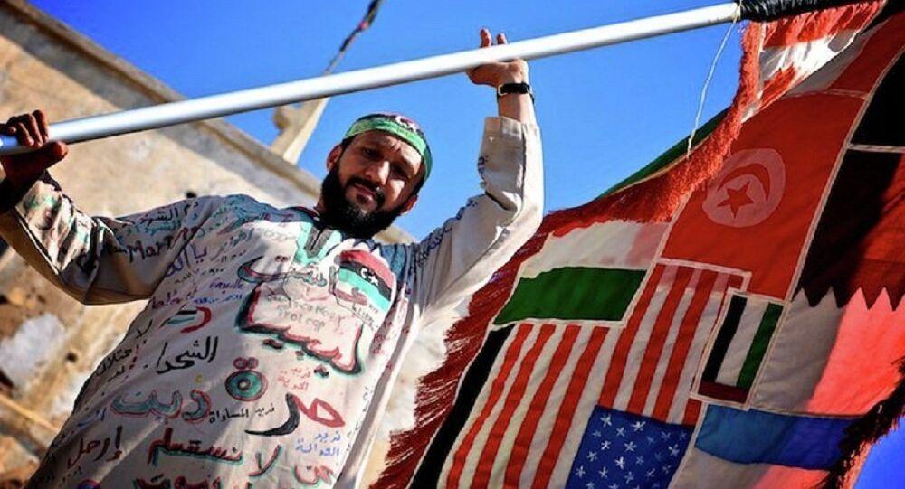 Un uomo tiene la bandiera di tutti i paesi coinvolti nella guerra civile in Libia