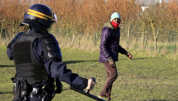 Agente di polizia ferma un migrante a Calais - Sputnik Italia