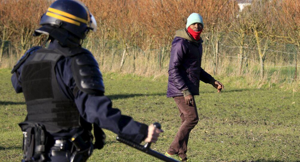 Agente di polizia ferma un migrante a Calais