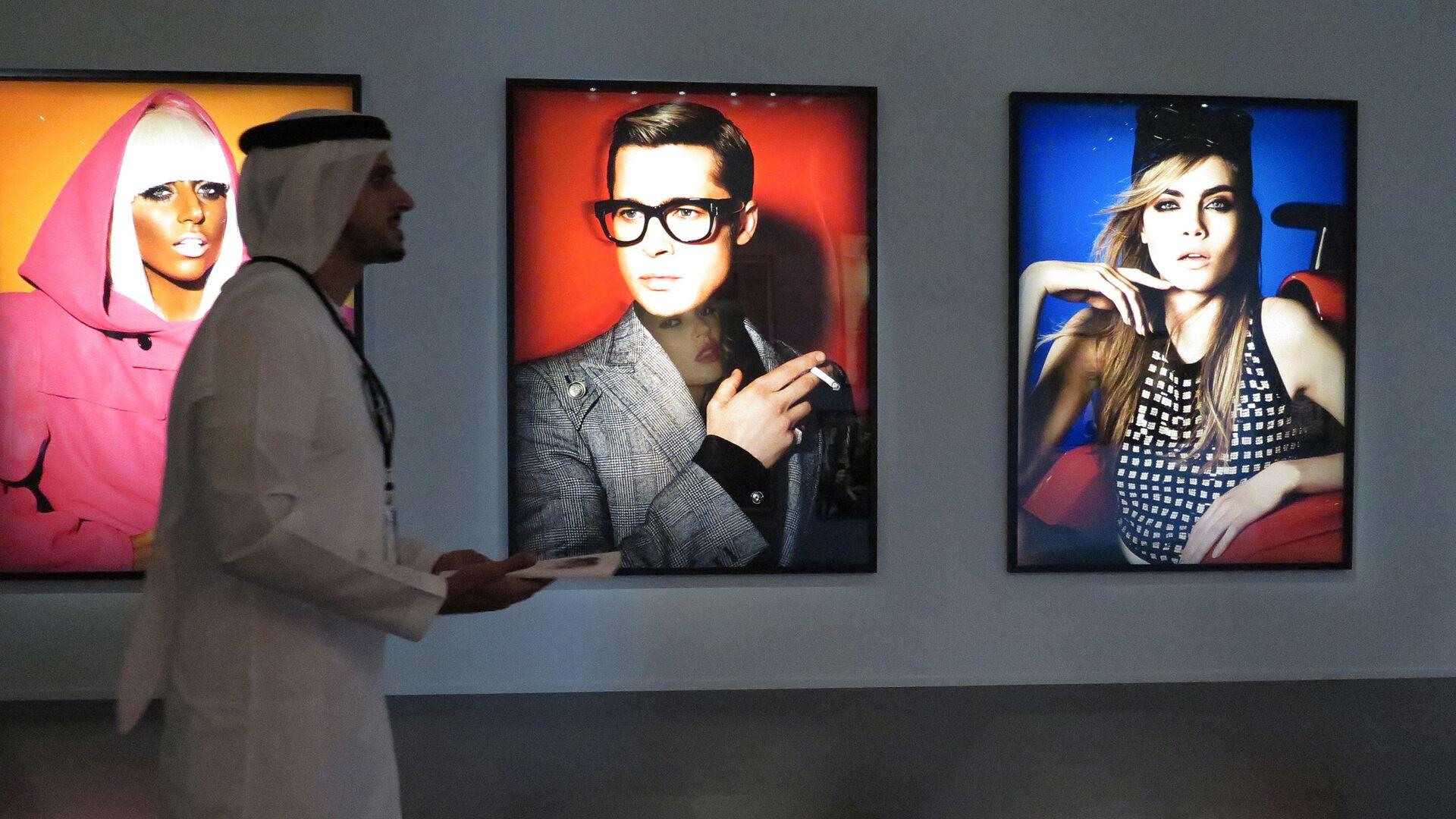 Посетитель фотовыставки в Дубае проходит мимом коллекции Heat перуанского фотографа и дизайнера Mario Testino  - Sputnik Italia, 1920, 07.07.2021