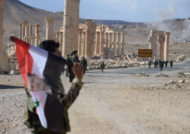 Soldato siriano tra le rovine di Palmira dopo la liberazione