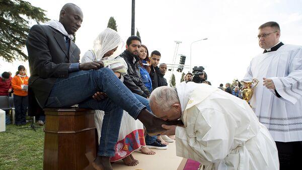 Papa Francesco bacia un piede a un profugo durante il rituale della lavanda dei piedi - Sputnik Italia