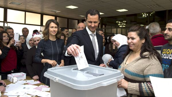 Syria's President Bashar al-Assad (C) casts his vote next to his wife Asma (centre left) inside a polling station during parliamentary elections in Damascus, Syria - Sputnik Italia