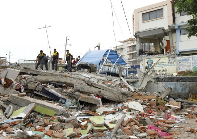 Police officers stand on debris after an earthquake struck off Ecuador's Pacific coast, at Tarqui neighborhood in Manta April 17, 2016