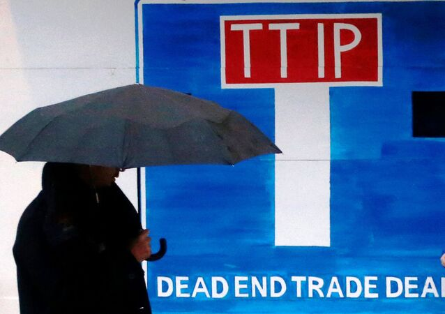 A pedestrian walks past a wooden blockade built by Greenpeace activists at the main entrance of a conference center where negotiators are expected to discuss the 12th Round of the Transatlantic Trade and Investment Partnership (TTIP) in Brussels, Belgium, February 22, 2016.