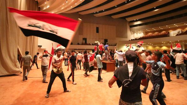 Iraqi protesters wave national flags as they gather inside the parliament after breaking into Baghdad's heavily fortified Green Zone on April 30, 2016 - Sputnik Italia