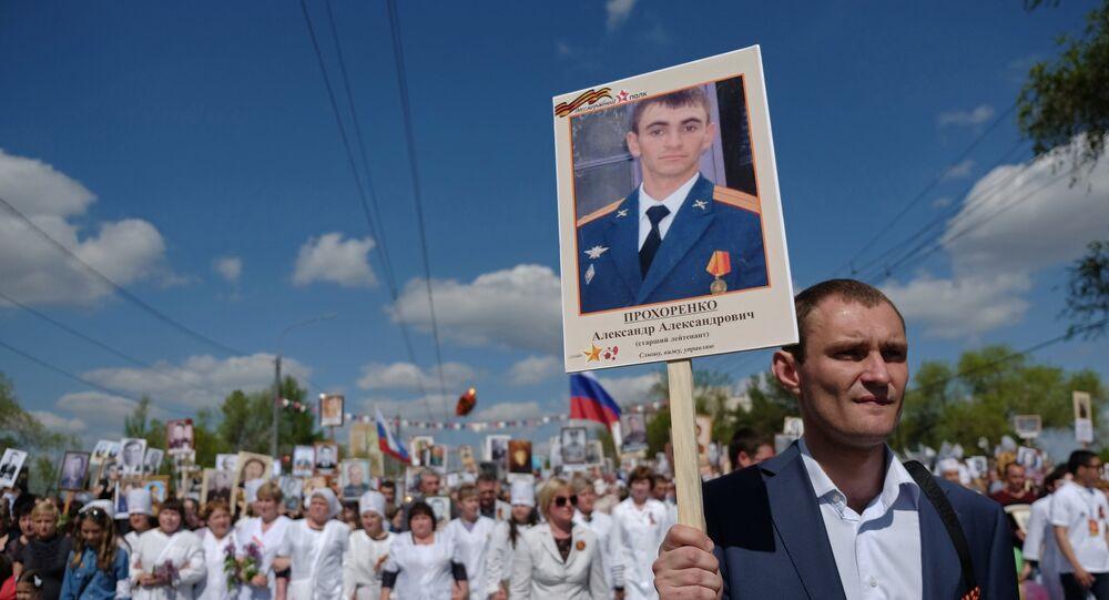 Un partecipante della manifestazione Bessmertny Polk ad Orenburg, Russia, porta la foto di Alexander Prokhorenko, il paracadutista acquisitore russo morto durante la liberazione di Palmira.
