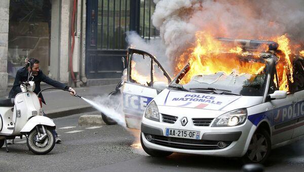 Мужчина пытается потушить полицейскую машину во время беспорядков в Париже, Франция - Sputnik Italia