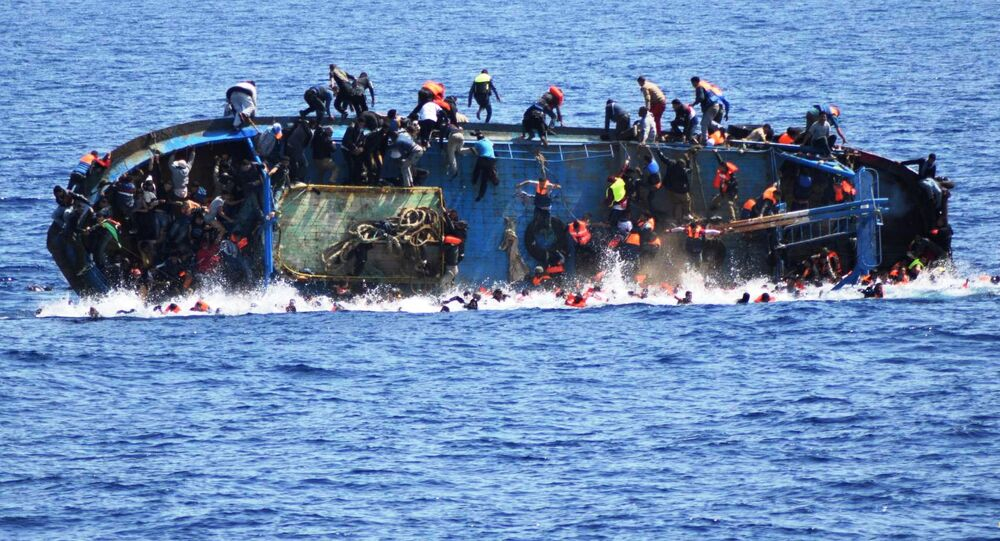Migrants are seen on a capsizing boat before a rescue operation by Italian navy ships Bettica and Bergamini off the coast of Libya in this handout picture released by the Italian Marina Militare on May 25, 2016.