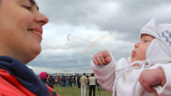 Una mamma tiene in braccio la sua bambina mentre sullo sfondo è in corso l'esibizione delle Frecce Tricolori. - Sputnik Italia
