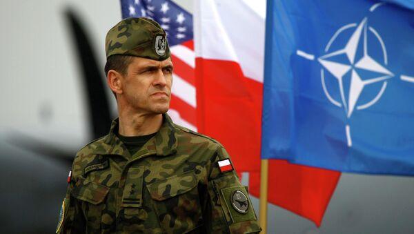 Un soldato polacco di fronte alle bandiere degli USA, della Polonia e della NATO a Swidwin in Polonia del Nord - Sputnik Italia