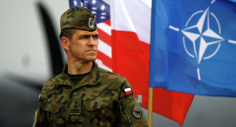 Un soldato polacco di fronte alle bandiere degli USA, della Polonia e della NATO a Swidwin in Polonia del Nord