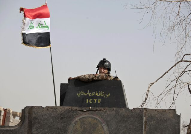 A soldier from Iraq's elite counterterrorism forces looks from the gun turret of a Humvee as troops gather on the edge of the Shuhada neighborhood in Islamic State-held Fallujah, Iraq