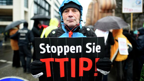 A protester holds up a sign, reading: Stop TTIP! (Transatlantic Trade and Investment Partnership) - Sputnik Italia