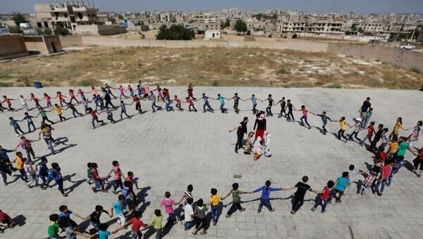 Students form a circle as they play during a celebration marking the end of the school year, at 'Syria, The Hope' school on the outskirts of the rebel-controlled area of Maaret al-Numan town, in Idlib province, Syria June 1, 2016 - Sputnik Italia