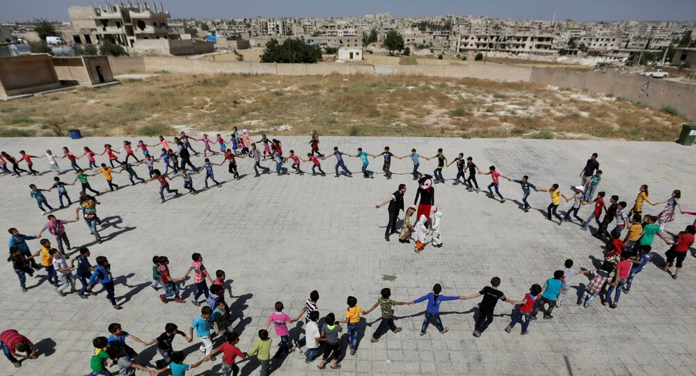 Students form a circle as they play during a celebration marking the end of the school year, at 'Syria, The Hope' school on the outskirts of the rebel-controlled area of Maaret al-Numan town, in Idlib province, Syria June 1, 2016