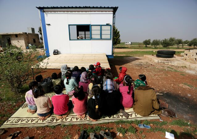 Children watch as volunteer teachers perform a puppet show inside a mobile educational caravan for children who do not have access to schools on the outskirts of the Syrian rebel-held town of Saraqib, Idlib province March 10, 2016