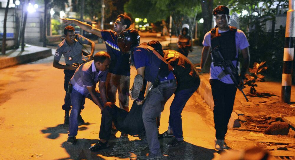 People help an unidentified injured person after a group of gunmen attacked a restaurant popular with foreigners in a diplomatic zone of the Bangladeshi capital Dhaka, Bangladesh, Friday, July 1, 2016.