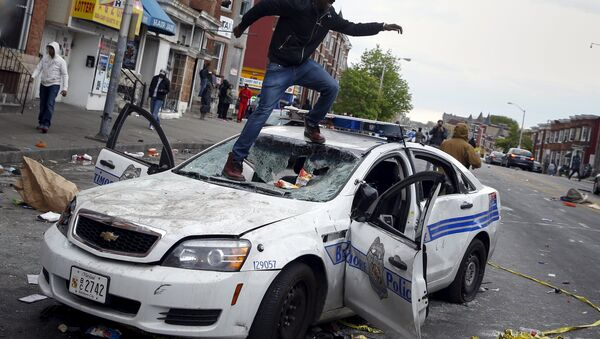 Demonstrators jump on a damaged Baltimore police department vehicle during clashes in Baltimore, Maryland April 27, 2015 - Sputnik Italia