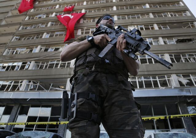 A Turkish special forces policeman stands guard in front the damaged building of the police headquarters which was attacked by the Turkish warplanes during the failed military coup last Friday, in Ankara, Turkey, Tuesday, July 19, 2016