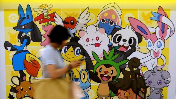 A woman using a mobile phone walks past a shop selling Pokemon goods in Tokyo, Japan July 20, 2016. - Sputnik Italia