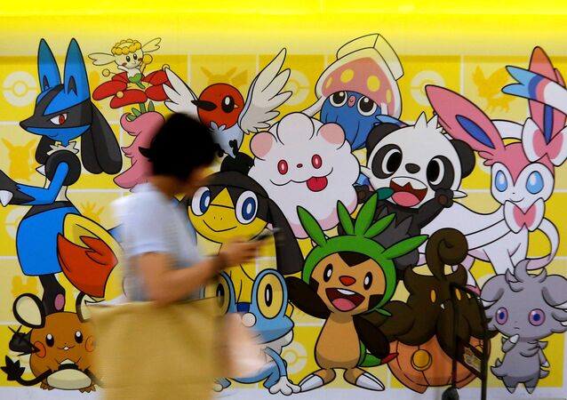 A woman using a mobile phone walks past a shop selling Pokemon goods in Tokyo, Japan July 20, 2016.