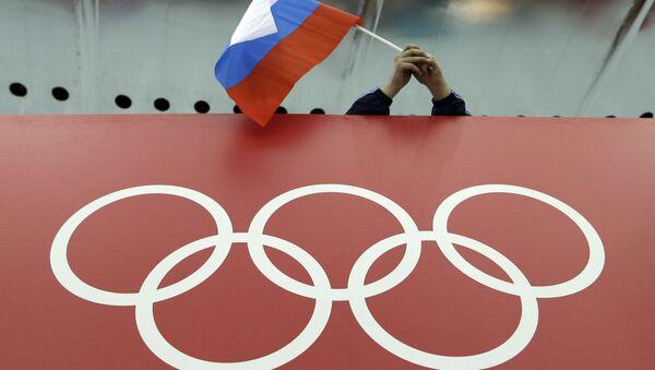 Un tifoso tiene la bandiera russa sopra il logo delle Olimpiadi. (Foto d'archivio) - Sputnik Italia