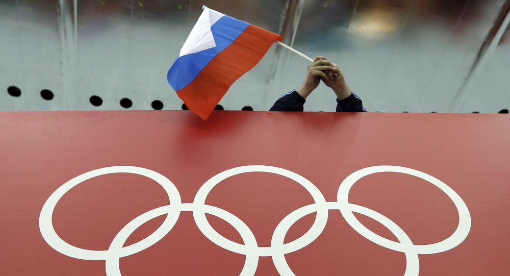 Un tifoso tiene la bandiera russa sopra il logo delle Olimpiadi. (Foto d'archivio)