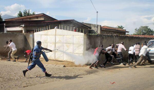 Un poliziotto del Burundi spara spray urticante contro dei manifestanti. - Sputnik Italia