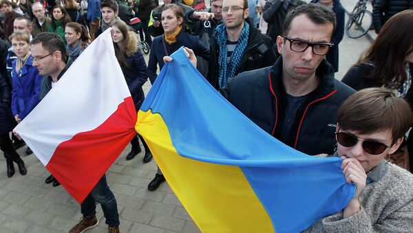 People holding a Poland flag, left, and a Ukraine flag listen to speakers during a demonstration in Warsaw, Poland showing their support for protesters in Ukraine - Sputnik Italia