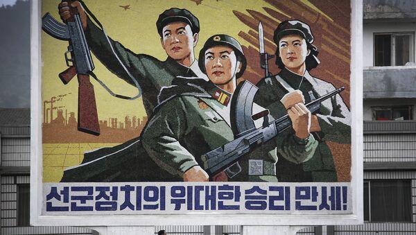 Corea del Nord, la gente passa sotto il poster `Evviva la vittoria della politica dell'esercito prima di tutto`` nel centro della città di Wonsan. - Sputnik Italia