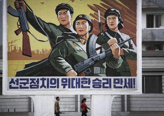 Corea del Nord, la gente passa sotto il poster `Evviva la vittoria della politica dell'esercito prima di tutto`` nel centro della città di Wonsan.