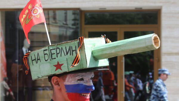 Un sostenitore del Partito Comunista con un tank in testa e la scritta su BerlinO - Sputnik Italia