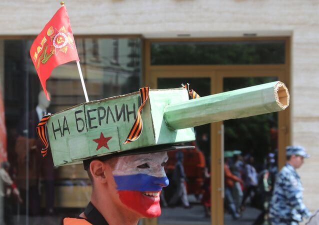 Un sostenitore del Partito Comunista con un tank in testa e la scritta su BerlinO