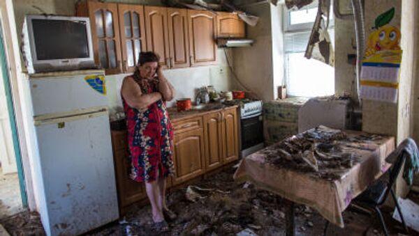 Una donna osserva disperata il suo appartamento distrutto dalle bombe a Donetsk. - Sputnik Italia