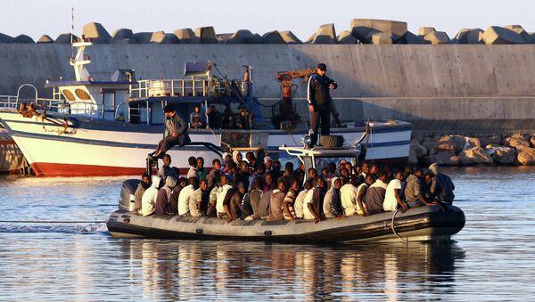 Migranti su una delle tante carrette del mare in navigazione nel mare tra la Libia e l'Italia. - Sputnik Italia